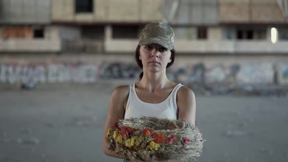 Thumbnail for Portrait of a Beautiful Girl in a Camouflage Cap and White T-shirt Holding a Wreath