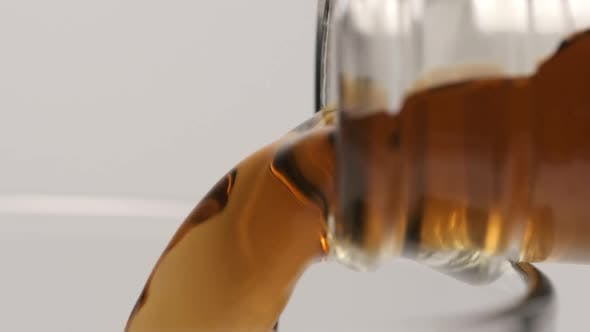 Thumbnail for Macro shot of pouring of a brown beverage from a glass bottle