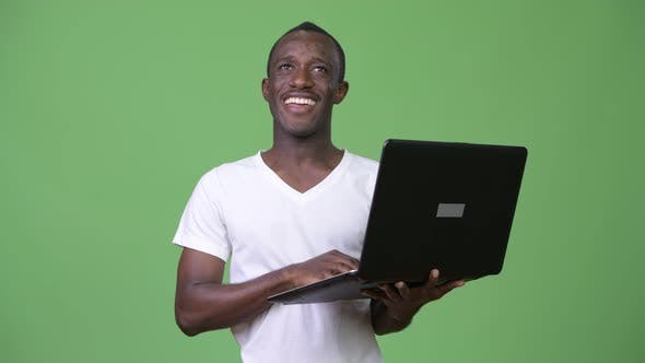 Thumbnail for Young Happy African Man Thinking While Using Laptop