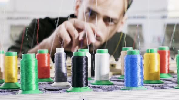 Thumbnail for Man in a Fabric Factory Checking the Sewing Thread