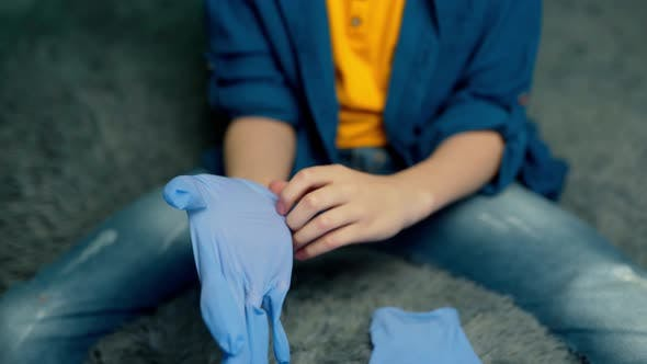 Thumbnail for The boy puts on rubber gloves