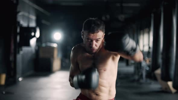 A Muscular Sportsman is Boxing in the Dark Gym