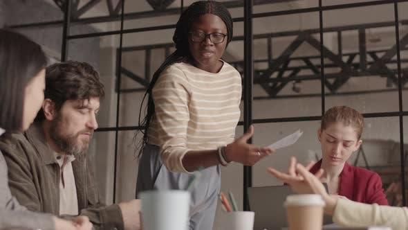 African Woman Handing in Papers