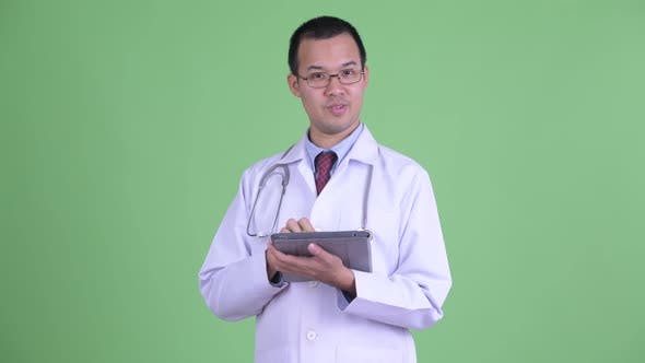 Thumbnail for Happy Asian Man Doctor Talking While Using Digital Tablet
