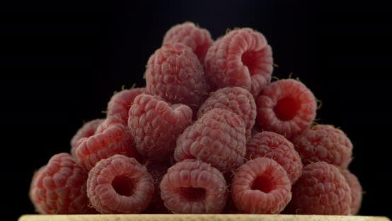 Thumbnail for Ripe Raspberry Berries Piled on A Plate, Rotated Against a Black Background