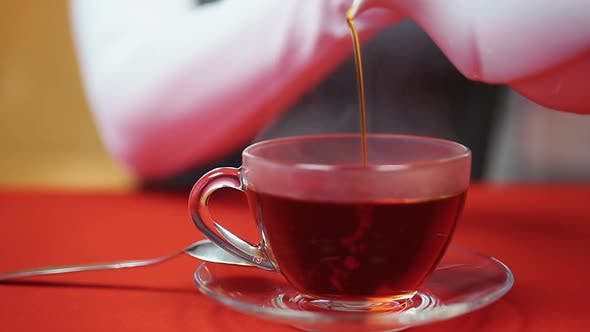 Thumbnail for Relaxing Evening at Home. Woman Pouring Tea in a Cup. Hot and Tasty Beverage