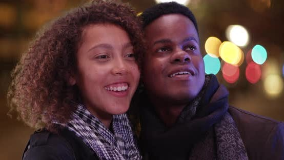 Young African American couple admire the nightlife of the city