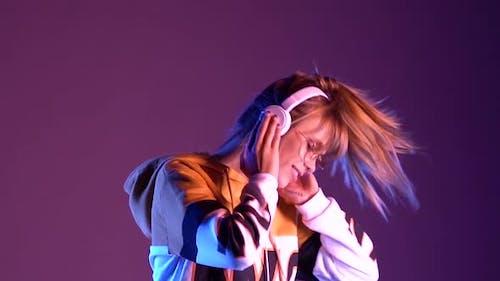 Happy Teen Girl Wear Headphones Listen Music Dance in Purple Neon Slow Motion
