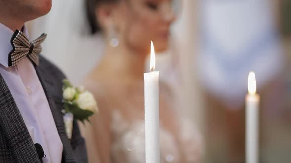 Newlyweds. Caucasian Bride and the Groom Stand in Church with Candles at Wedding Ceremony