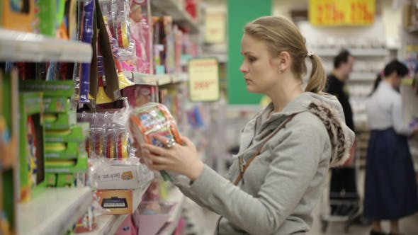 Thumbnail for Young Woman is Choosing Toys in the Supermarket