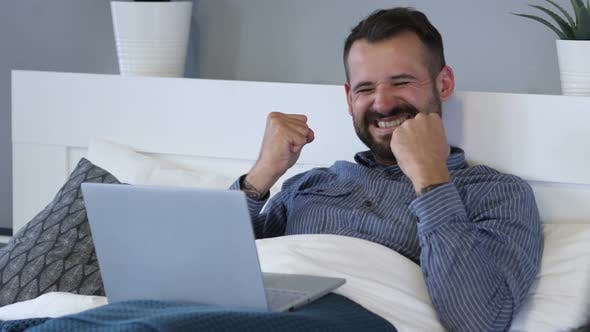 Cover Image for Reaction of Success by Happy Man Using Laptop in Bed