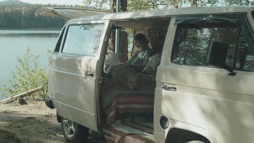 Woman and Dog Resting in Travel Trailer
