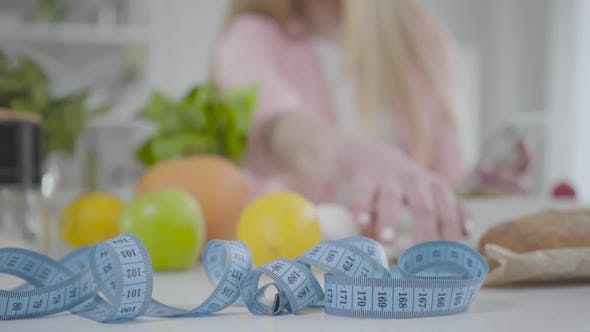 Close-up of Measuring Tape Lying on the Table with Blurred Caucasian Girl Counting Calories