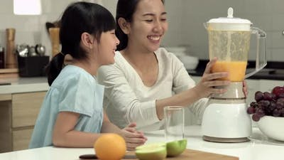 Mother and daughter making orange smoothie