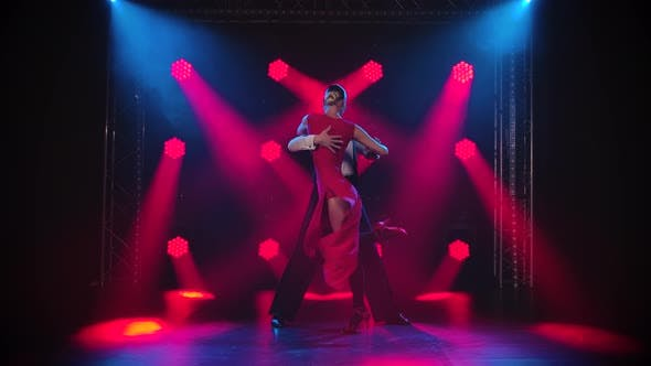 Thumbnail for Young Couple Passionately Dancing Tango in a Dark Room with Smoke and Red Spotlights in Slow Motion.
