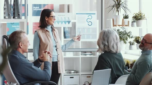 Thumbnail for Young Business Lady Giving Presentation to Mixed-Aged Colleagues