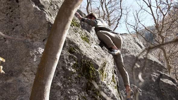 Junger Mann klettert an die Spitze des großen Felsbrocken