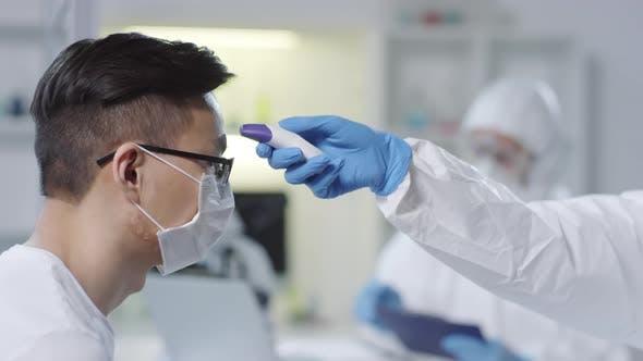 Thumbnail for Unerkennbarer Arzt, der die Temperatur des ansteckenden Patienten überprüft