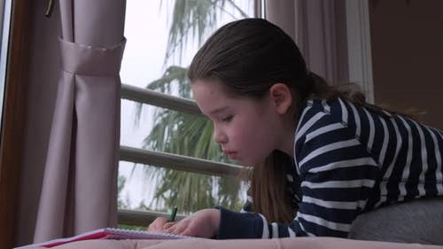 A Little Girl Drawing with Pencils at Home