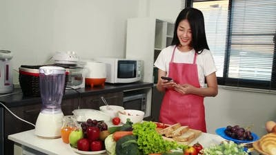 woman using mobile phone in kitchen room