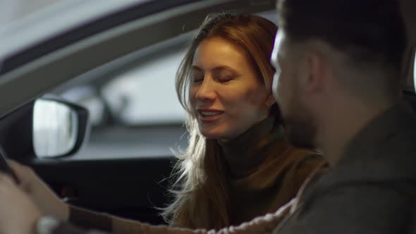 Thumbnail for Cheerful Couple Inspecting Interior of Car