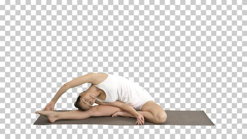 Beautiful young woman wearing white clothing doing yoga exercise