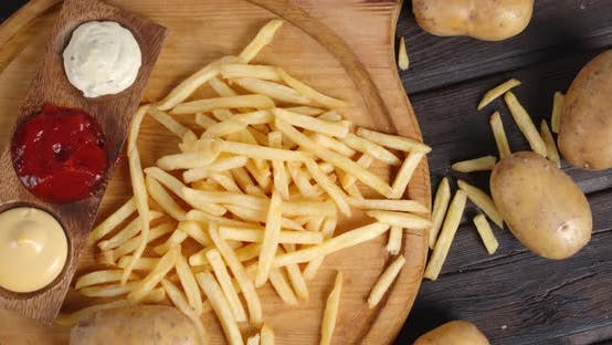 French Fries with Sauce on a Cutting Board Rotates Slowly.