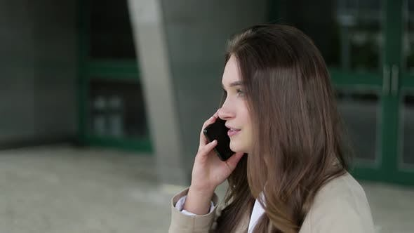 Thumbnail for Attractive Girl Outside Talking on Phone, Looking Serious