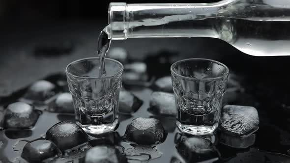 Thumbnail for Pouring Up Shots of Vodka From a Bottle Into Glass. Black Background