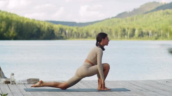 Fit Woman Practicing Yoga on Lake Pier