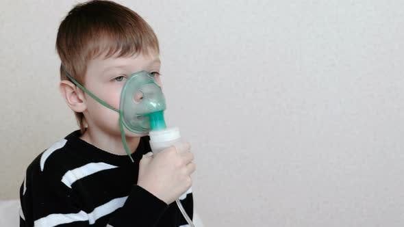 Thumbnail for Using Nebulizer and Inhaler for the Treatment. Boy Inhaling Through Inhaler Mask