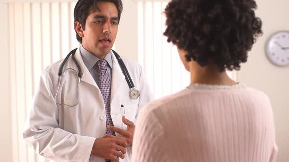 Hispanic doctor talking to female patient