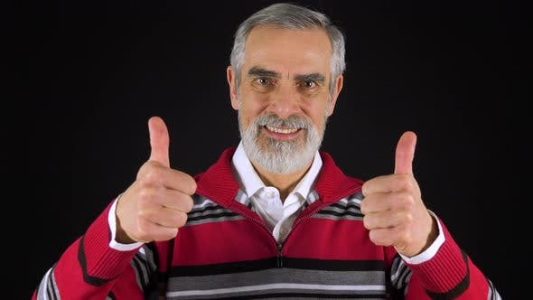 Thumbnail for An Elderly Man Smiles and Shows a Double Thumb Up To the Camera - Black Screen Studio