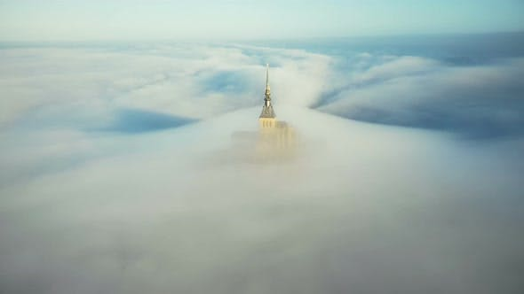 Drone Flying Away From Ethereal Mont Saint Michel Castle Spire Covered By Atmospheric Sunrise Mist