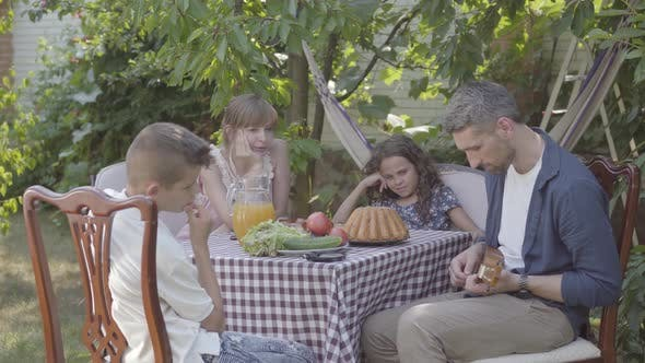 Thumbnail for Father Plays the Guitar for His Family at a Dinner Table Sitting in the Backyard. Friendly Family