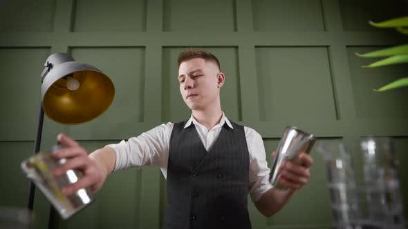 Thumbnail for A Handsome Male Bartender Performs Tricks with a Shaker. A Professional Throws and Catches a Shaker.