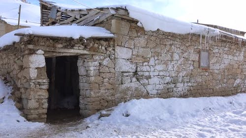 Snowy Stone Wall Village House and Barn Door in Heavy Continental Climate of Winter Season