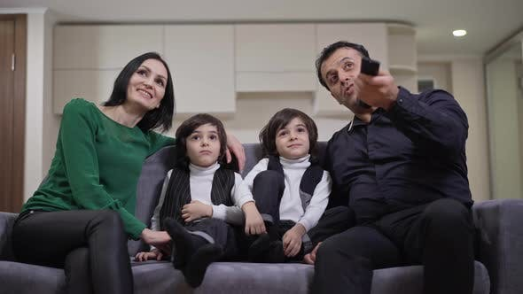 Front View of Positive Multiethnic Family Watching TV Sitting on Couch in Living Room at Home