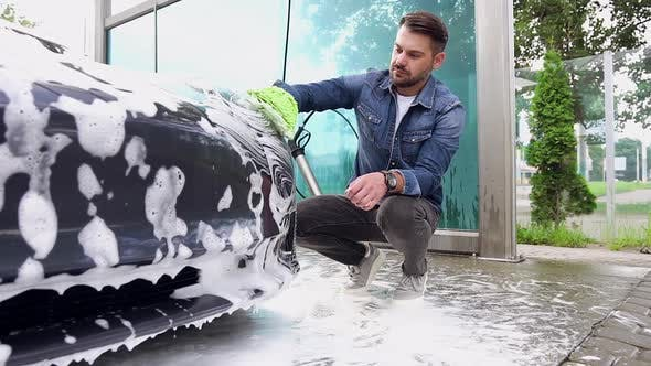 Cover Image for Bearded Guy which Squatting Near His Trendy Car and Washing Headlights with Foamy Sponge in Car Wash
