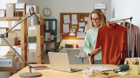 Thumbnail for Verkäuferin demonstriert Kunden Kleidung beim Web-Anruf