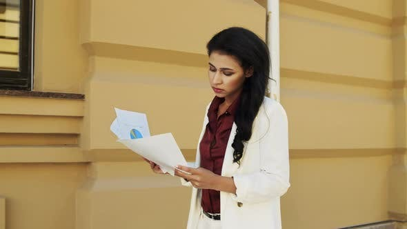 Confident Business Woman Examining Paperworks Outdoors