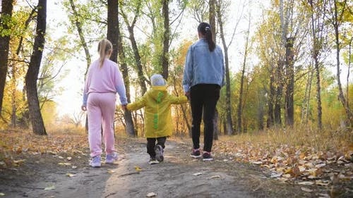 Mother and Two Children Walking in the Park and Enjoying the Beautiful Autumn Nature. Happy Family