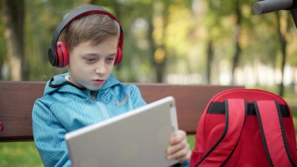 Thumbnail for Engrossed Caucasian Boy in Headphones Gaming Online on Tablet Sitting in Autumn Park Outdoors