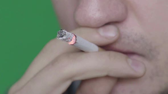 Thumbnail for Cigarette in the Mouth of a Smoker. Close-up. Slow Motion. Chroma Key. Green Background.