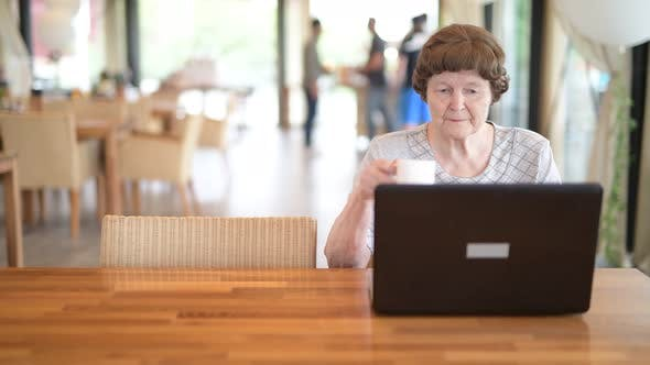 Cover Image for Senior Woman Drinking Coffee While Using Laptop At The Coffee Shop
