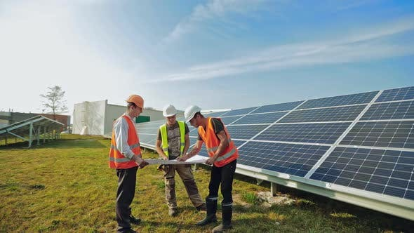 Male technicians with a project plan on a solar farm