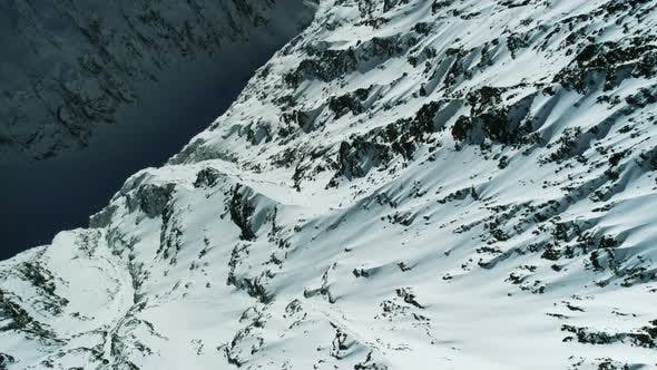 Thumbnail for Flight Over Rocky Alpine Mountains Valley Full Of Snow