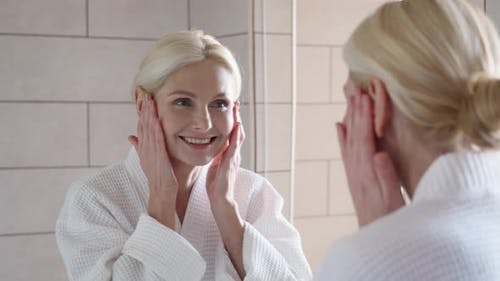 Happy Smiling Mid Age Blond Woman Standing Looking at Mirror