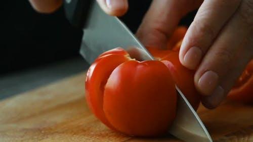 Schneiden von Tomate von Culinary Knife. Zeitlupe