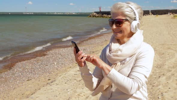 Thumbnail for Old Woman in Headphones with Smartphone on Beach